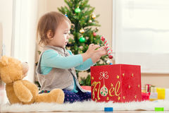 Little girl playing with her presents under Christmas tree. Little toddler girl playing with her presents under the Christmas tree Royalty Free Stock Photo