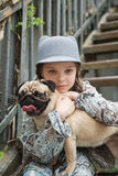 Little girl playing with her pug dog outdoors in rural areas in. Little kid girl playing with her pug dog outdoors in rural areas in summer Royalty Free Stock Images