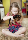 Little girl and puppy. Little girl is playing with her puppy at home Royalty Free Stock Photo
