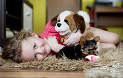 Little girl and puppy. Little girl is playing with her puppy at home royalty free stock image