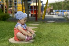 Little girl playing with her sandals sitting on the green grass stock photography