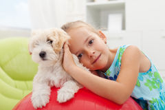 Little girl playing with her small fluffy dog. At home Stock Photos