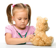 Little girl is playing with her teddy bear Stock Photo