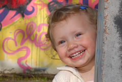 Little girl playing hide and seek. Portrait of a smiling little girl playing hide and seek. Colorful painted wall in the background Royalty Free Stock Image