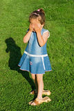 Little girl playing hide-and-seek. Playful little girl wearing slip-on and playing hide-and-seek Stock Photography