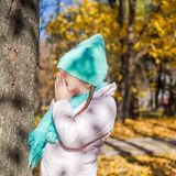 Little girl playing hide and seek in the autumn. Forest. This image has attached release Stock Photos
