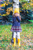 Little girl playing hide and seek in autumn forest. Little girl playing hide and seek near the tree in autumn forest Stock Images