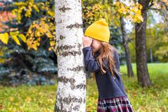Little girl playing hide and seek in autumn forest. Little girl playing hide and seek near the tree in autumn forest Royalty Free Stock Photos