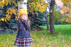 Little girl playing hide and seek in autumn forest. Little girl playing hide and seek near the tree in autumn forest Royalty Free Stock Photography