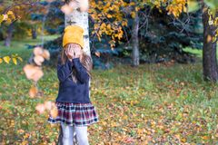 Little girl playing hide and seek in autumn forest Stock Photos