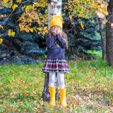 Little girl playing hide and seek in autumn forest. Little girl playing hide and seek near the tree in autumn forest Stock Photography