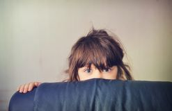 Little girl playing hide and seek behind the sofa. Bed Stock Photos