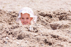 Little girl playing hide and seek hidden in a hole. Little girl in a big hat hidden in a hole on the beach with only her head sticking out Stock Photos
