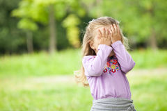Little girl is playing hide-and-seek hiding face. Little girl hiding face outdoor portrait Stock Photo