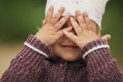 Little girl is playing hide-and-seek. Hiding face Stock Photos