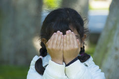 Little girl is playing hide-and-seek. Hiding face Stock Images