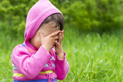 Little girl is playing hide-and-seek. Hiding face Royalty Free Stock Photography
