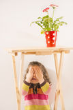 Little girl is playing hide-and-seek hiding face. Cute little girl hiding under the table covering her face with her hands, red vase with flower on table, studio Stock Images