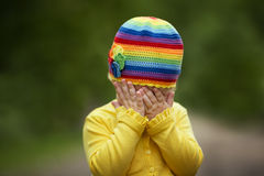 Little girl is playing hide-and-seek hiding face. Little girl with rainbow hat is playing hide-and-seek Stock Photography
