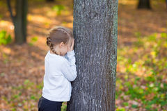 Little girl playing hide and seek near the tree in. Little girl playing hide and seek in autumn forest outdoors Stock Photo