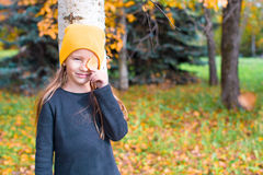 Little girl playing hide and seek near tree in Royalty Free Stock Image