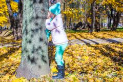 Little girl playing hide and seek near the tree in. Autumn park. This image has attached release Stock Photos