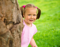 Little girl is playing hide and seek outdoors Royalty Free Stock Images