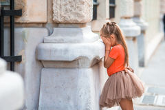 Little girl playing hide and seek on street in Europe outdoors. Little girl playing hide and seek on street in Paris outdoors Royalty Free Stock Image