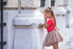 Little girl playing hide and seek on street in Paris outdoors Stock Photography