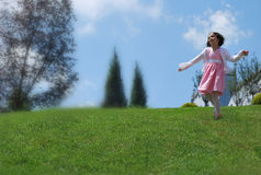 A little girl playing on the hill Stock Image