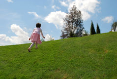 A little girl playing on the hill Royalty Free Stock Photo