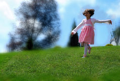 A little girl playing on the hill Royalty Free Stock Images