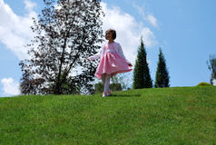 A little girl playing on the hill Stock Photography