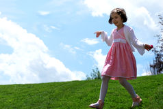 A little girl playing on the hill Stock Photo