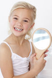 Little girl playing holding a mirror Stock Image
