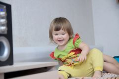 Little girl playing at home happy smiling. On bed stock photography