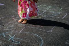Little girl playing hopscotch in driveway Royalty Free Stock Photos