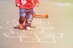 Little girl playing hopscotch on the street Stock Photography