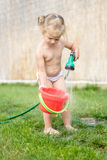 Little girl playing with hose and water Stock Photography