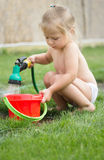 Little girl playing with hose and water Royalty Free Stock Image