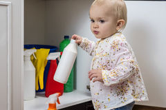 Little girl playing with household cleaners Stock Image