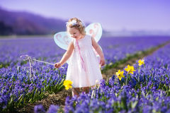 Little girl playing in hyacinth field Royalty Free Stock Photo