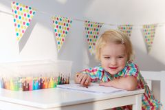 Little girl playing indoors drawing with colorful pencils Stock Image