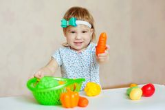 Little girl playing indoors at home or kindergarten. Adorable smiling little child cutting plastic vegetables. Healthy royalty free stock image