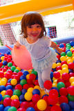 Little girl playing in inflatable bouncing castle Stock Photos