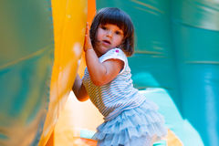 Little girl playing in inflatable bouncing castle Stock Image