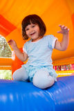 Little girl playing in inflatable bouncing castle. Little white girl having fun in the bouncing castle at bright summer day Royalty Free Stock Image