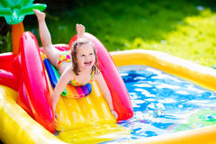 Little girl playing in inflatable garden swimming pool Royalty Free Stock Images