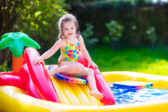 Little girl playing in inflatable garden swimming pool Stock Photography