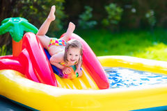 Little girl playing in inflatable garden swimming pool Stock Photos